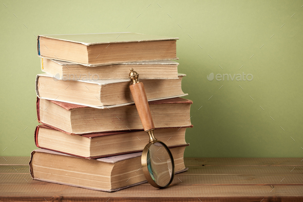 Stack of old books and magnifying glass on wooden table - Stock Photo - Images
