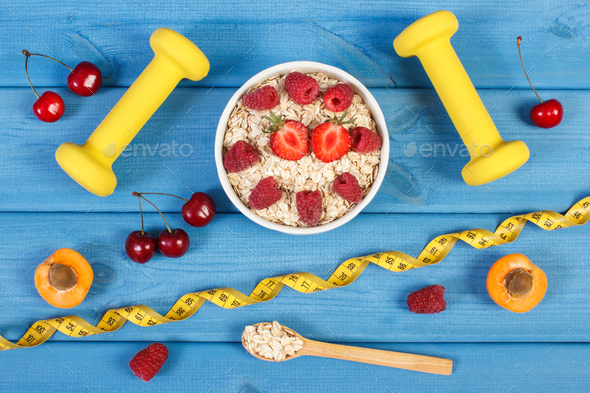 Oat flakes with fruits, dumbbells and centimeter, concept of slimming and healthy lifestyle - Stock Photo - Images