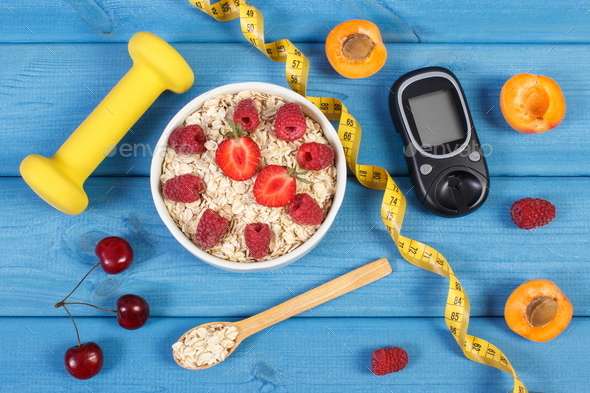 Glucose meter for measuring sugar level, oatmeal with fruits and dumbbells - Stock Photo - Images