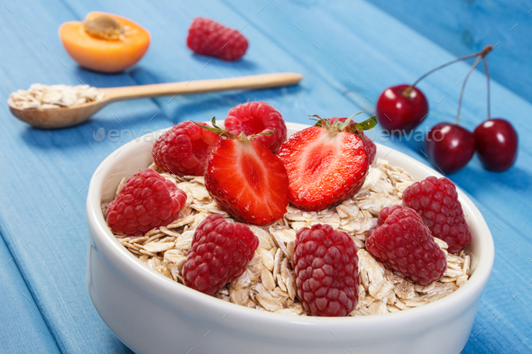 Oat flakes or oatmeal with strawberries and raspberries, healthy lifestyle and nutrition - Stock Photo - Images