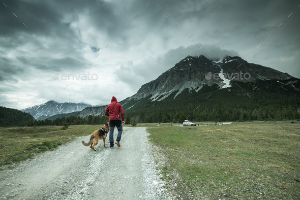 Man with dog trekking mountains in Switzerland - Stock Photo - Images