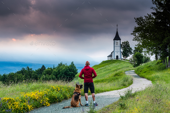 Man with dog looking at  Church of  St. Primus and Felician, Jam - Stock Photo - Images
