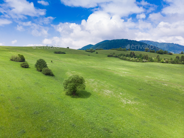 Aerial drone view over green hills and blue sky - Stock Photo - Images