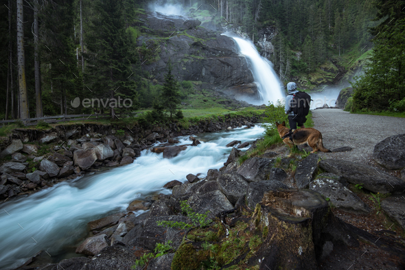 Man and dog watching Krimml Waterfalls in High Tauern National P - Stock Photo - Images
