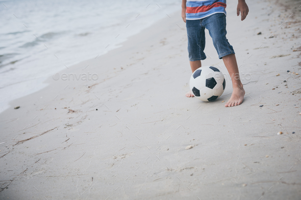 Young little boy playing on the beach with soccer ball. - Stock Photo - Images