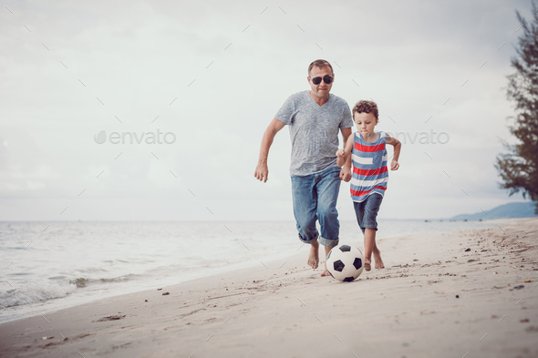 Father and son playing football on the beach at the day time. - Stock Photo - Images