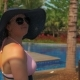Beautiful Girl in a Blue Hat on a Lounger By the Pool - VideoHive Item for Sale