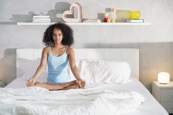 Young African American Woman Doing Yoga In Bed After Sleep - Stock Photo - Images