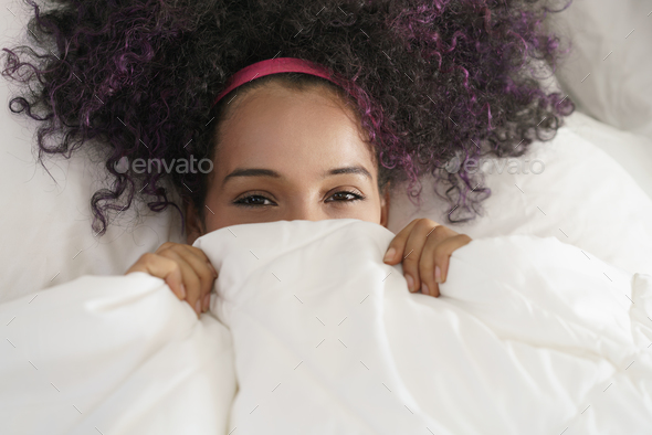 Beautiful Happy Hispanic Teen Waking Up And Smiling Undercover - Stock Photo - Images