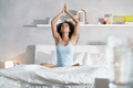Young African American Woman Doing Yoga In Bed After Sleep - PhotoDune Item for Sale