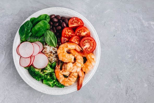 Shrimp Burrito Bowl with brown rice, spinach, radish, black beans, tomato and broccoli. - Stock Photo - Images