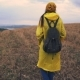 Traveler Woman Walking in field. Girl Wearing Yellow Raincoat with Backpack - VideoHive Item for Sale