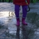 Cute Little Girl with Colorful Umbrella Is Jumping in Puddles in Park at Sunset. - VideoHive Item for Sale