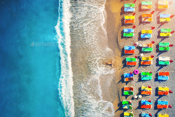 Aerial view of lying woman on the beach with colorful chaise-lounges - Stock Photo - Images