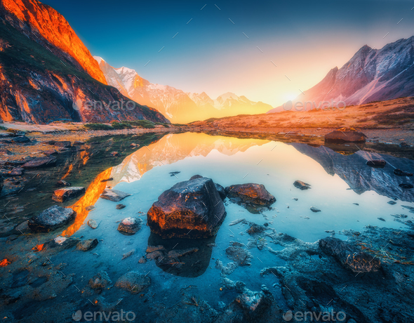 Mountains with illuminated peaks, stones in mountain lake at sunset - Stock Photo - Images