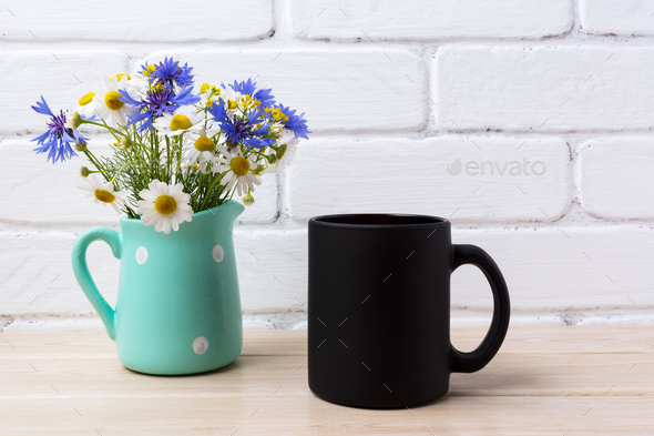 Black coffee mug mockup with cornflower and daisy in pitcher - Stock Photo - Images