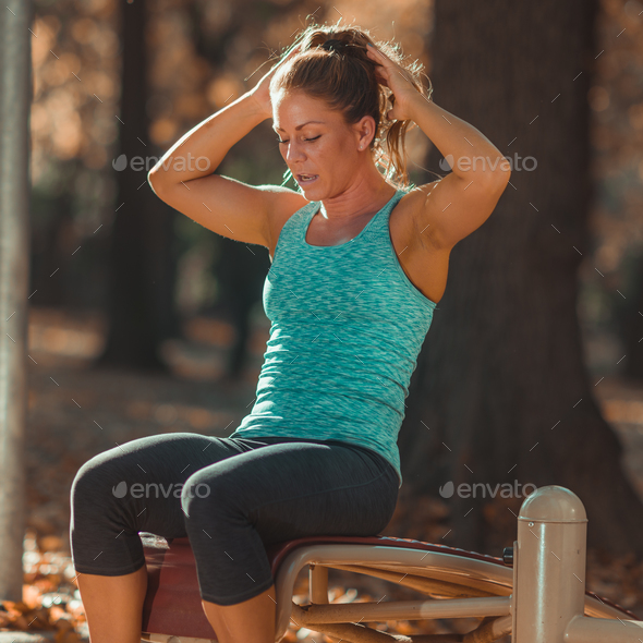 Woman doing sit ups in the park, in the fall - Stock Photo - Images