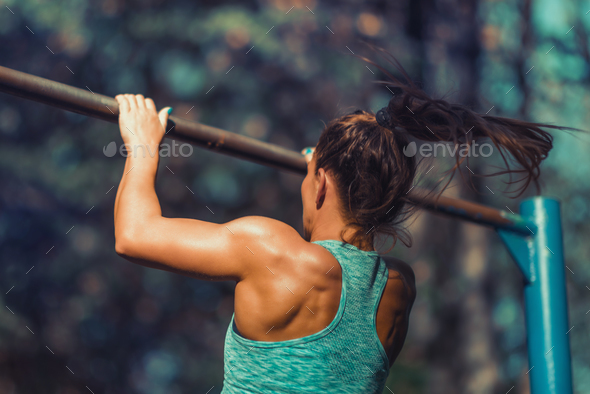 Woman Exercising on Horizontal Bar Outdoors in The Fall - Stock Photo - Images