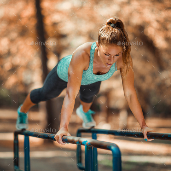 Woman Exercising on Parallel Bars Outdoors in The Fall - Stock Photo - Images