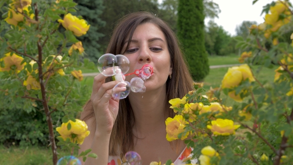 Smiles Young Happy Caucasian Woman Blowing Bubble In The Park With Blossom  Rose (Stock Footage) 7ecbd45a4