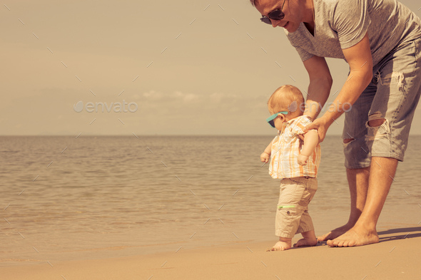 Father and baby son playing on the beach at the day time. - Stock Photo - Images
