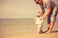 Father and baby son playing on the beach at the day time. - PhotoDune Item for Sale