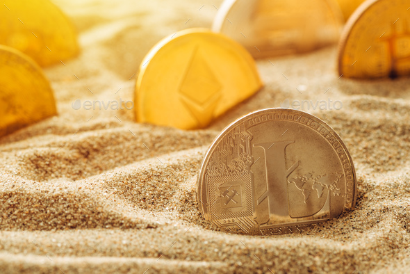 Silver Litecoin coin in sand - Stock Photo - Images