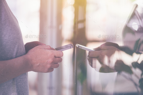 Using mobile phone in front of store shop window - Stock Photo - Images
