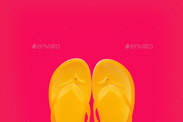 Yellow beach flip flops on neon pink background - Stock Photo - Images