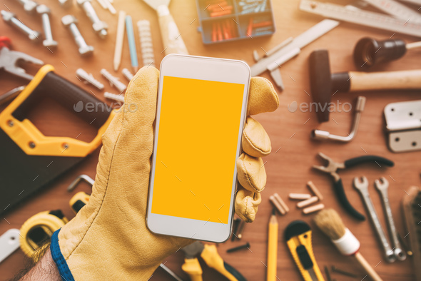 Maintenance handyman smartphone app, repairman holding mobile ph - Stock Photo - Images