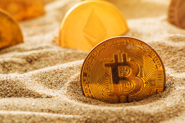 Golden bitcoin in sand - Stock Photo - Images