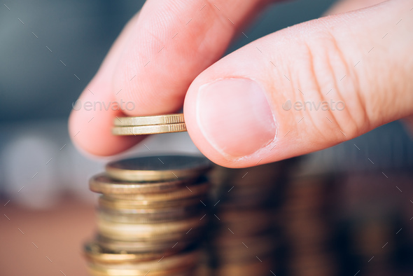 Close up of male hand stacking coins - Stock Photo - Images