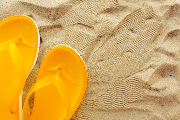 Yellow beach flip flops on sand - Stock Photo - Images
