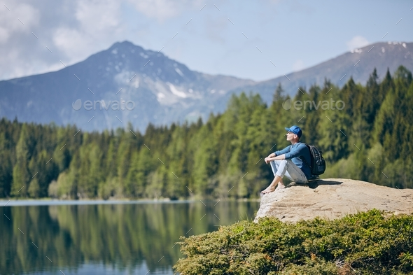 Tourist resting on rock above lake - Stock Photo - Images