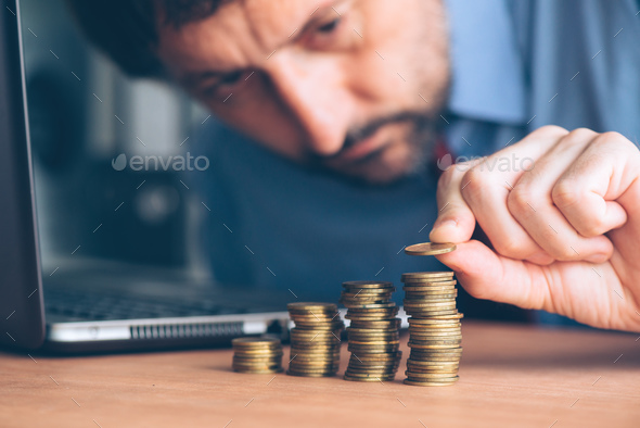 Finances and budgeting, businessman stacking coins - Stock Photo - Images