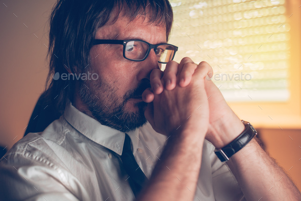 Close up face portrait of concentrated businessman thinking - Stock Photo - Images