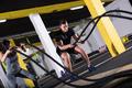 sports couple doing battle ropes cross fitness exercise - PhotoDune Item for Sale