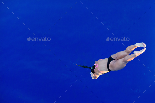 Female diver jump into the pool - Stock Photo - Images