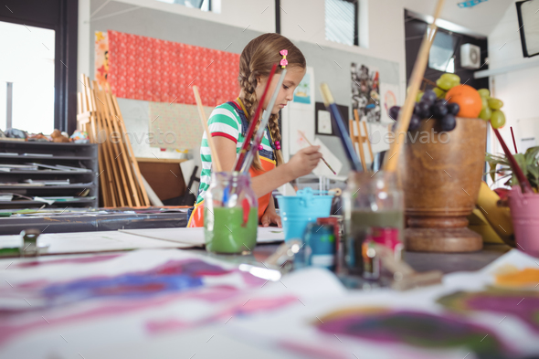 Girl painting in classroom - Stock Photo - Images