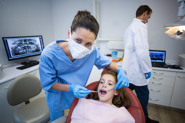 Dentist examining a young patient with tools - Stock Photo - Images