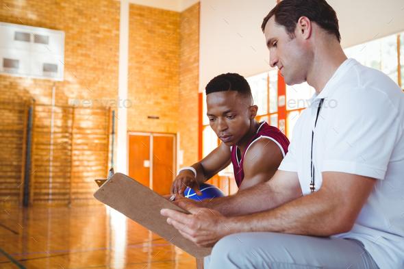 Coach explaining to basketball player - Stock Photo - Images