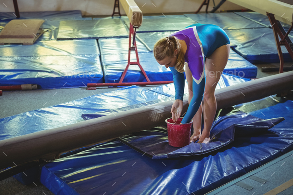 Female gymnast applying chalk powder on her hands before practicing - Stock Photo - Images