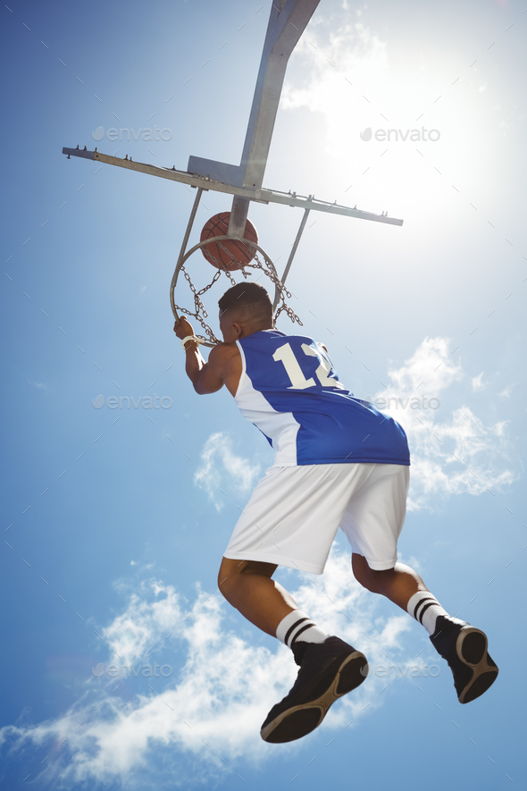 Rear view of male teenager hanging on basketball hoop - Stock Photo - Images