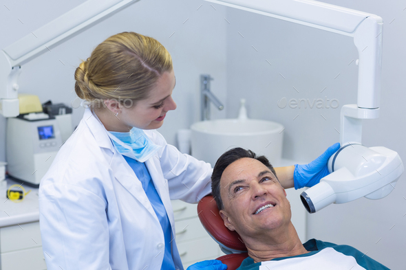 Dentist examining a male patient with dental tool - Stock Photo - Images