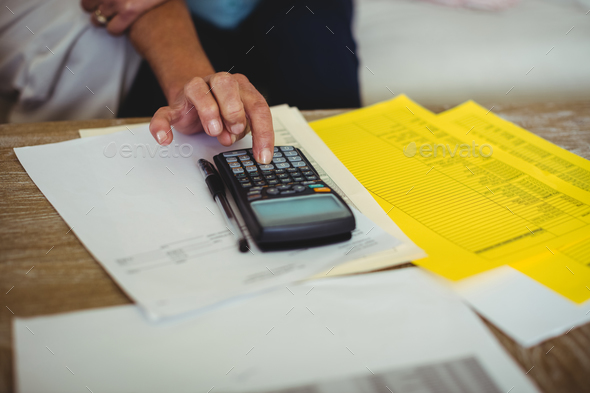 Senior couple calculating bills in living room - Stock Photo - Images