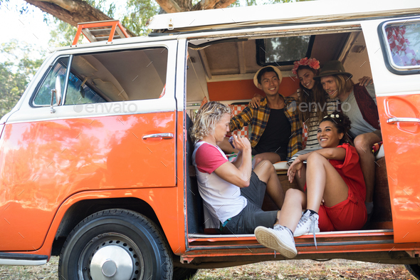 Happy friends sitting together in camper van - Stock Photo - Images
