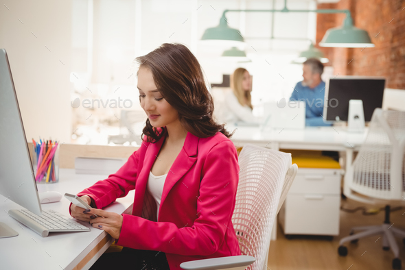 Female executive using mobile phone at desk - Stock Photo - Images