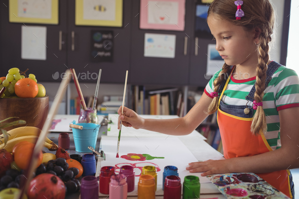 Concentrated girl painting at desk - Stock Photo - Images