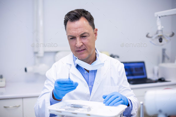 Dentist checking tools in dental clinic - Stock Photo - Images