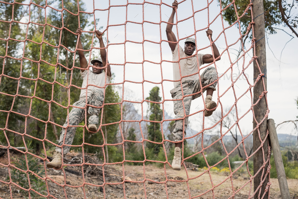 Military soldiers climbing a net during obstacle course - Stock Photo - Images